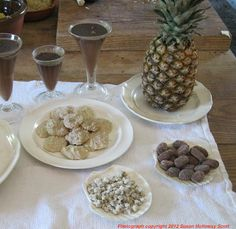 In the fluted glasses are chocolate creams, like chocolate pudding. The pineapple represents fresh fruit. Below the pineapple is a dish of chocolate almond conceits. The conceit is that there are no almonds in the recipe, but simply chocolate (and sugar and butter, much like fudge) shaped like almonds, and dusted with sugar. Next is a small dish of caraway comfits, especially popular with a decanter of port. Last of the desserts is a plate of Ratafia (fruit flavored brandy) cakes (biscuits).