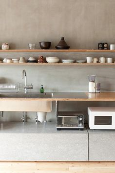 Two long plywood shelves line a concrete wall above an industrial looking Ted countertop in a Tokyo apartment by Naruse Inokuma Architects.