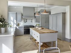 Traditional country shaker kitchen in grey. Light grey shaker-style kitchen cabinets with copper accents and oak chevron flooring and island worktop. Traditional range cooker with chimney hood and Carrara Marble effect composite kitchen worktops. Wood Kitchen Island, Wood Floor Kitchen, Wood Kitchen Cabinets, Painting Kitchen Cabinets, Kitchen Flooring, Kitchen Worktops, Oak Worktops, Kitchen Units, Country Kitchen