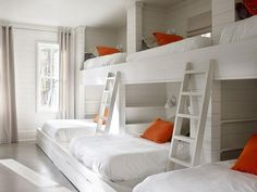 Country bunk room features a shiplap walls lined with a wall of three side by side built-in bunk ...