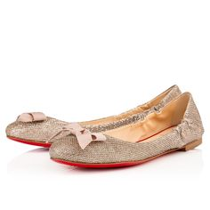 """The red sole meets the must-have ballerina silhouette with """"Gloriana."""" This ladylike slip-on is perfect for everyday in gold glitter luminor with a nude ribbon bow."""