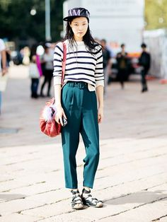 A striped sweater is worn with teal trousers, strappy sandals, and a baseball hat