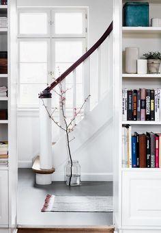 Kig fra stue til gang med gråt linoleumsgulv, vase med blomsterkvist og flot istandsat trappe