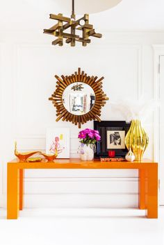 Orange lacquered console with modern light fixture and mirror