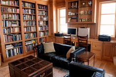 Office with built-in wood shelves, chest and leather couch