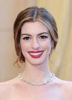 Updos Lookbook: Anne Hathaway wearing Loose Bun (118 of 120). At the 2011 Academy Awards, host Anne Hathaway opted for a classic beauty look: ravishing red lips and a center-parted bun at the nape of her neck. Loose, romantic tendrils frame her face and keep the look from feeling overdone.