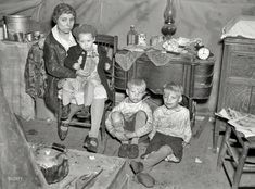 """April 1937-Flood refugee family in tent at Tent City near Shawneetown, Illinois. """"Is that a toy motorcycle on the floor to the mother's right? The youngest has a doll. And mother saved her sewing machine (a major investment and a tool for further savings by making things). Today, after the family members, what would we save? Photo albums? Computer disks with photos?""""  Photo by Russell Lee"""