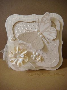 handmade card ... white on white butterfly  ... Spellbinders Label One dies to shape card and made frame ... butterfly with pearlescent embossing ... pearls galore ,,, organdy ribbon ... another masterpiece by Donna ... Hero Arts