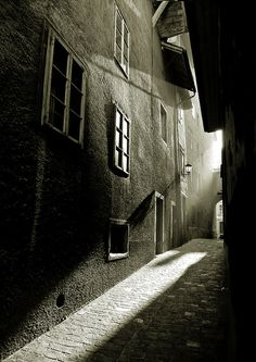 The strong light shows a pathway into some sort of town. It contrasts with the darkness.
