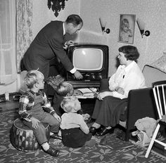Så er den lille familie klar til at tænde for fjernsynet.; A family is ready to watch televison.