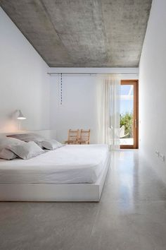 Concrete floor and ceiling, white walls and bed linen. Warm wood detail.