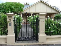 Rendered brick pillars and fence with iron work gate and fence panels