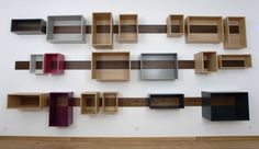 A wooden board is fixed on the wall and supports a number of boxes. They can be hanged, removed, slid freely, always changing the layout of the shelves.