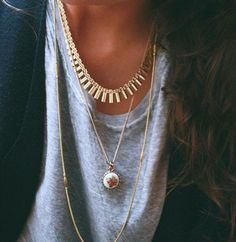 A grey shirt is paired with layering gold necklaces.