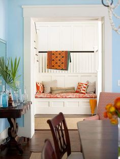 Beyond the dining room, a stylish built-in bench offers a spot to relax in the hallway. The unexpected nook is a comfortable place to read or catch up on the day's events. Graphic-pattern pillows create a common tie between several warm hues; the space blends red tones from the dining area with the living room's orange accents for a warm, zesty look./