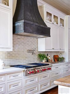A locally crafted zinc hood gives this kitchen wall a rustic and industrial element. The hood also helps to visually break up the white cabinetry and neutral backsplash./