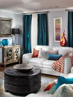 Textured throws, pillows and curtains in various textures in colors, including teal and orange, create dimension within the room.