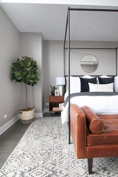A modern master bedroom in the city of Chicago. Gray walls, white bedding, and a 4 post bed. Absolutely adore this space! Love the faux fiddle leaf fig in the corner to bring some life to the space.