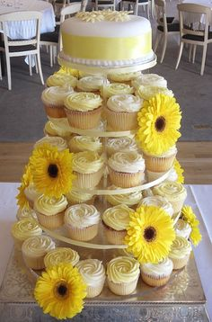 pale yellow cake and cupcakes decorated with yellow gerber daisies