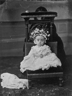 A dead infant on a velvet cushion. The adult lurking in the background was no doubt there to hold the baby's head upright. Still, it does provide a creepy, ominous feel to the photo, as if death itself is crouched back there.