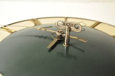A stunning deep green art deco wooden wall clock made in Germany circa 1930 by Kienzle.  Its clockwork operated and the key included with purchase is the original!  The clock has been tested and it s working perfectly. It measures 24 cm (9.2 inches) in diameter.  - - - - - - - - - - - - - - - - - - - - - - - - - - - - - - - - - - - - - - - - - - - - - - - - - - - - - - - -  Please take a closer look at all photos for the best idea of its condition.  Keep in mind that all items in our shop…