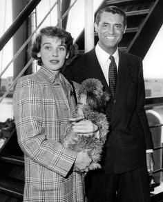 Cary Grant, recovering from a recent seige of yellow jaundice during which he lost 40 lbs., is met by wife Betsy Drake and French poodle, Suzy, as he pulls into the Los Angeles Harbor aboard the Dutch freighter Dalerdyk. June, 1949