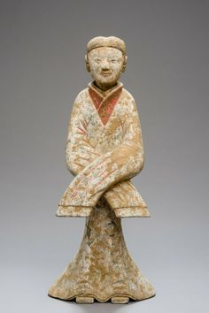 """TERRACOTTA FIGURE IN DANCE POSE, cold painting. China, in the style of Han dynasty, H 54.7 cm Figure form a burial gift, dark grey ceramic, painted with colors on a white ground; the figure depicting a maid, clad in a floor long, wide robe, the long hair combed back; shown in a dance pose Changxiuwu (""""dance with the long sleeves), displaying fine, sensuous features, remnants of painting (black and red pigments), encrustations."""