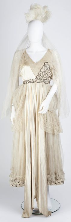 An Edwardian cream satin court dress, with lace bodice insert and sleeves and flouncing to skirt, fully decorated with thread work flowerheads and foliate sprays, accompanied by a plume of feathers headdress with tulle veil. Mallams Auctioneers, via the saleroom (link: https://www.the-saleroom.com/en-gb/auction-catalogues/mallams-ltd-oxford/catalogue-id-srmalla10045/lot-285efbfa-90ad-4eee-8b3f-a5ad01119c3a).