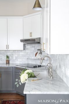 Two-toned gray and white cabinets, marble subway tile, Carrara countertops, a big farmhouse sink, and brass hardware give this kitchen a classic yet modern look. #kitchedecor #homedecorideas #subwaytile #whitekitchen