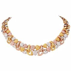 Adorn your neck with this glamorous and exquisite diamond heart necklace. Finely crafted in solid 18K yellow, white and rose gold, this necklace features a heart design that is accented with some 290 round cut diamonds approx. 4.50 ct, G-H color, VS clarity, 325 round cut GIA Graded natural light to Fancy light pink diamonds approx. 5.70 ct and 345 round cut Fancy yellow to fancy intense yellow diamonds approx. 6.35 ct. This alluring and stunning necklace features a high polished finish and…