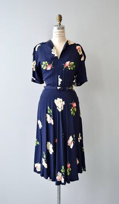 Vintage 1940s dark navy rayon dress with sparsely placed large floral print, small hook and eye clasp at the collar so that it may be worn open or closed, short sleeves, matching belt and metal side zipper. --- M E A S U R E M E N T S ---  fits like: medium bust: 40-42.5 waist: 30-31: hip: