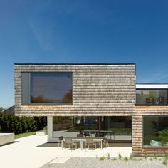 House featuring a concrete base and cedar shingle-clad upper walls