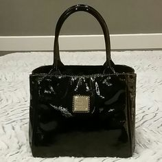 """PRICE DROP Dooney & Bourke Patent Baby Satchel Dooney & Bourke black patent leather baby satchel with gold accents.  Bag is approx. 8"""" L x 7"""" H x 6"""" W with 5"""" handle drop.  Pink and white fabric lining with zip and cell phone pockets along with key clip.  Top magnetic closure.  Gently used twice in excellent condition.  Very faint scratches on D&B logo.  Light marks on interior which are only visible if lining is turned inside out and inspected closely.  Adorable bag holds more than you'd…"""