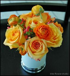 Orange- roses, ranunculus, hypericum berries in silver cup