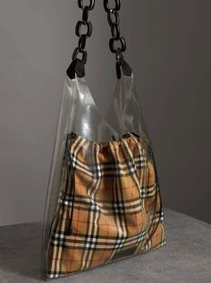 A #Burberry transparent shopper with a leather-wrapped chain handle and internal Vintage check cotton drawcord pouch