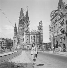 [Edith Ernst Vishniac standing in front of the Kaiser Wilhelm Memorial Church, corner of Marburgerstrasse and Tauentzienstrasse, Berlin 1947]