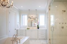 Chic white bathroom features an extra wide single vanity topped with white marble under a polished ...