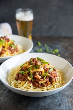 A portrait photo of two white bowls of Cowboy Spaghetti - chunks of ground sirloin, ,fire roasted tomatoes, fresh chopped green scallions and cheddar cheese - all topped with crumbled bacon. There is a beer visible out of focus in the back in a lager glass, and green scallions out of focus in the background net to the white bowl.