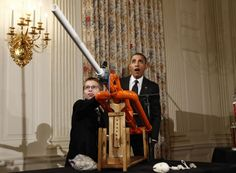 U.S. President Barack Obama reacts as Joey Hudy of Phoenix, Arizona, launches a marshmallow from his Extreme Marshmallow Cannon in the State Dining Room of the White House during the second White House Science Fair in Washington February 7, 2012. The fair celebrates the achievements of student winners of a broad range of science, technology, engineering and math (STEM) competitions from across the country. REUTERS/Kevin Lamarque