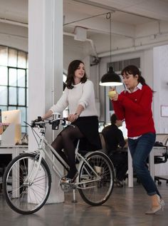 Anne Hathaway cycling around the office in The Intern movie
