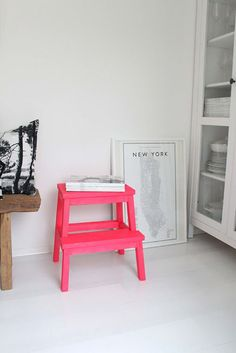 A small pink stool in a minimal white room five a big pop of color. How to decorate with the color pink.