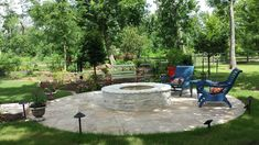 Travertine tile patio and stone fire pit with landscaping.