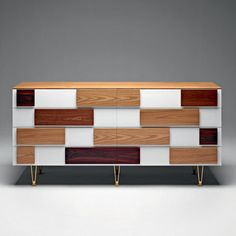 Cette commode équipée de nombreux tiroirs sans poignée a été imaginée par Gio Ponti entre 1952 et 1955. Sa façade à tiroirs met en relief différentes essences de bois ; orme, noyer italien, mahogany et bois de rose. Ici en version de 1,85 m de longueur.