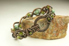 This is a solid copper hand crafted bracelet made using weaving techniques. The beads in the bracelet are purple goldstone, olive-green czech pressed glass and faceted faux turquoise beads. This is a medium 7 1/2 in. bracelet.