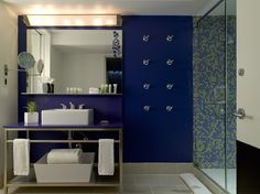 Modern Blue Bathroom  Bathroom with tiled walls and large glass shower screen with sink and unit underneath mirror.