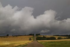 Drive Into the Storm is a prairie summer storm inspired image of a country road going straight into the turbulent horizon. Alberta Photography.