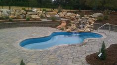 Vancouver Spa with custom boulder wall, natural stone waterfall and LED lighting. The decking is bullnose paver coping with tumbled paver decking. A fire pit was also built with custom natural stone benches. Landscape lighting really shows off the beauty of this pool.