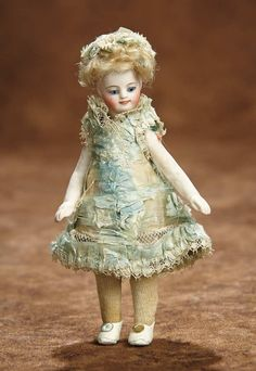 """5"""" French All-Bisque Mignonette with Rare Smiling Expression 1100/1500 Comments: for the French market, circa 1880, the little dolls were presented in the Parisian Etrennes catalogs at that time as """"poupees de poche"""" (pocket dolls) in reference to their miniature pocket-size stature. Value Points: very beautiful painting on all-original doll with rare smiling expression, wearing original aqua silk costume."""