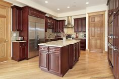 Angled View Of Kitchen Featuring A Combination Cherry Wood Cabinetry And Natural Flooring Doors