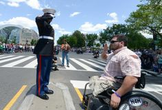 Double amputee United States Marine Corp Cpl. Sean Adams, of Gainesville, GA, salutes United States Marine Corp Sergeant Tim Chambers, as Chambers stood and saluted motorcyclist on the corner of 23rd Street and Constitution Ave in Northwest during the 25th anniversary of the Rolling Thunder Ride for Freedom at the base of the Memorial Bridge on Sunday, May 25. Khalid Naji-Allah/ Special for the Washington Times